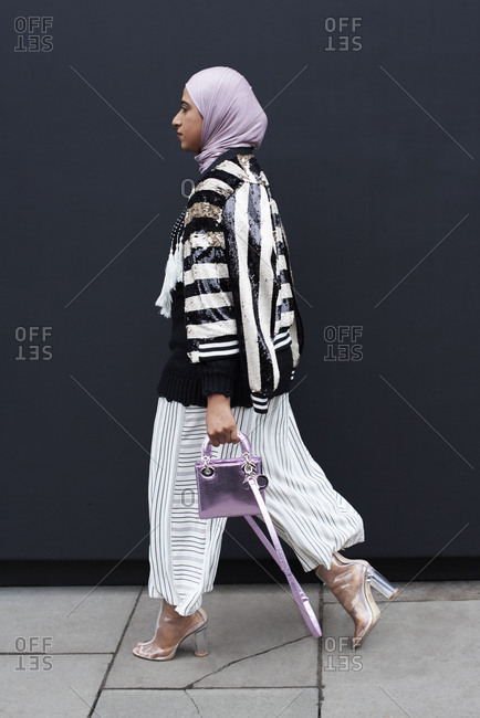 London, UK - February 21, 2017: Full length view of woman walking in a street wearing a hijab with black and white striped top, wide trousers and transparent high heel shoes, holding a small lilac metallic Dior handbag, London Fashion Week, day five.