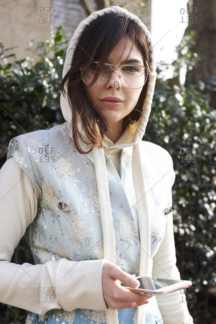 London, UK - February 20, 2017: Waist up portrait of fashion model, stylist and blogger Doina Ciobanu wearing a sleeveless blue and white patterned suit jacket and white hoodie, holding a smartphone outside Pringle of Scotland show, London Fashion Week, day four.