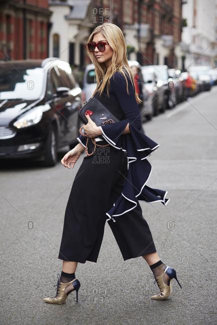 London, UK - February 20, 2017: Fashion blogger Natalia Georgala crossing street, London Fashion Week, day four.
