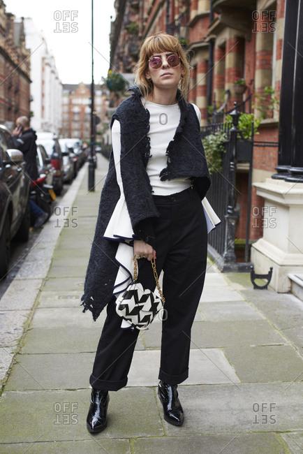 London, UK - February 20, 2017: Full length portrait of fashion blogger Xeni Kouveli standing in street holding Ferragamo handbag, London Fashion Week, day four.