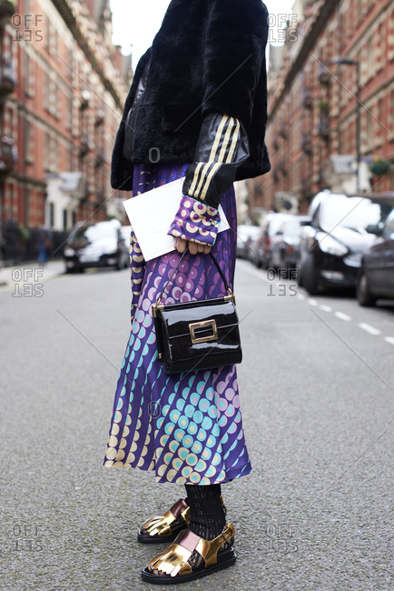 London, UK - February 20, 2017: Low section of woman standing in road wearing colorful print dress and metallic sandals, holding fashion show invite during London Fashion Week, vertical