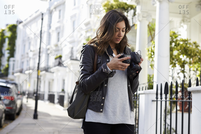Woman in the street looking at the screen on digital camera