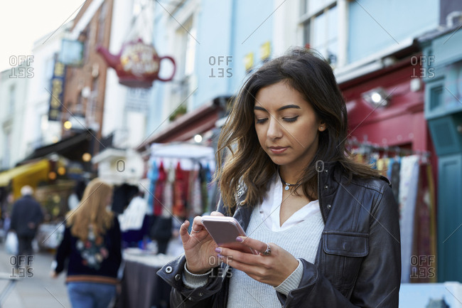 Young woman using phone in Portobello Road market, close up