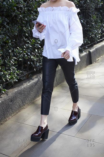 Low section of woman wearing white blouse walking in street