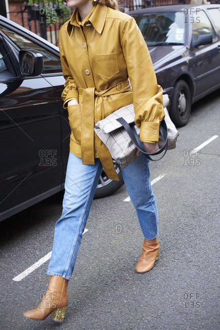 Woman in jeans carries large handbag, low section front view
