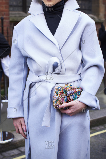 Woman wearing belted coat, holding small appliqu_ clutch bag