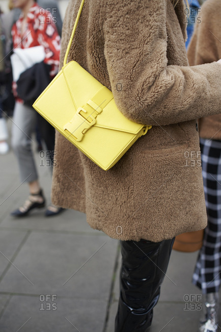 Woman in short brown coat with a yellow shoulder bag, mid section