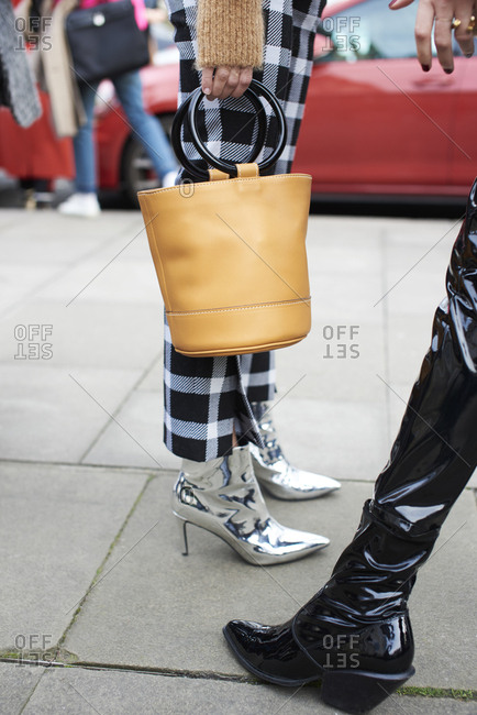 Low section of woman in silver boots holding bucket bag