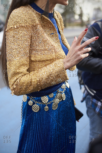 Woman in pleated skirt, short jacket and chain belt, side on