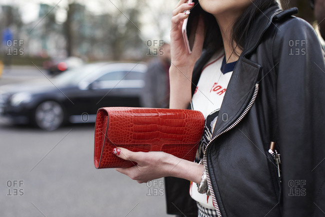 Woman in bike jacket holding red purse, close up mid section