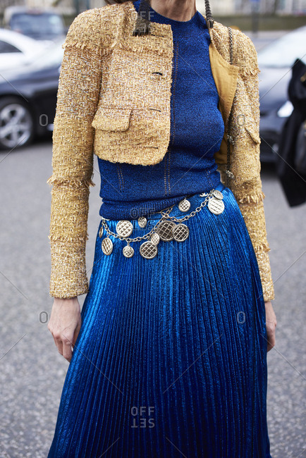 Woman in pleated skirt, short jacket and chain belt, front