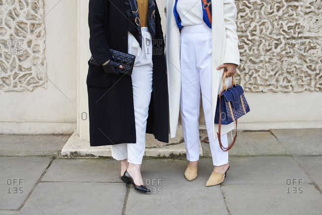 Two women in coats and white trousers standing in the street