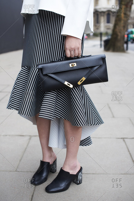 Low section of woman in striped skirt holding a clutch bag