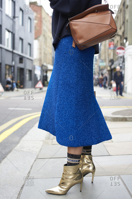 Woman in blue skirt and gold boots in street, low section