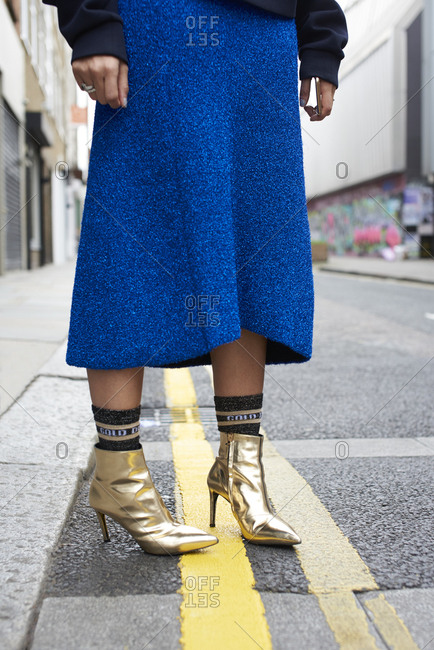 Woman wears blue skirt and gold boots in street, low section