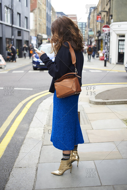 Woman in blue skirt and gold boots using phone in the street