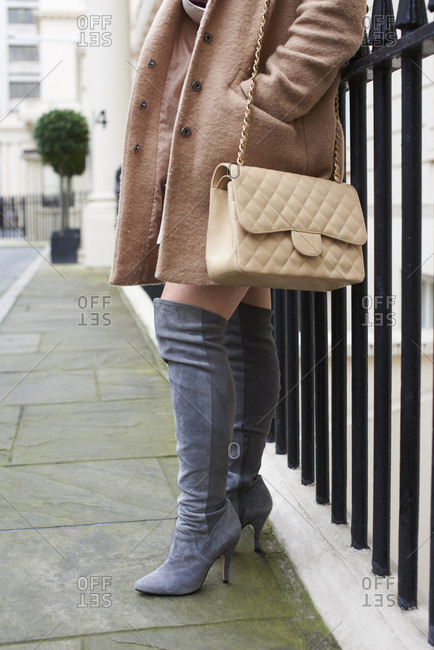Woman with designer handbag leaning, low section side view