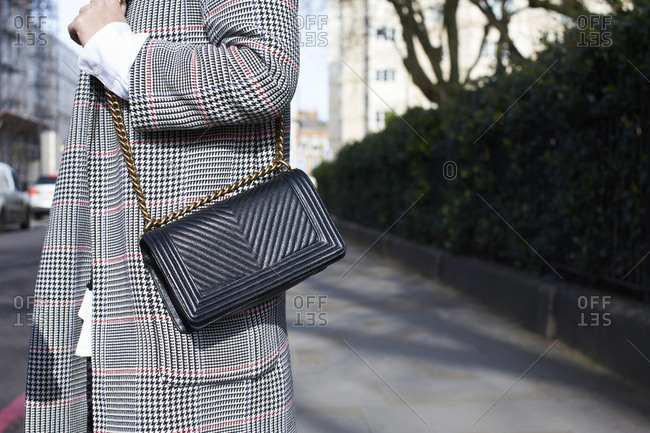 Woman in check coat with cross body handbag, horizontal