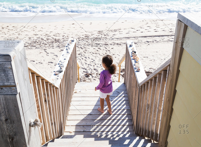 Young girl walking down stairway to a bright beach
