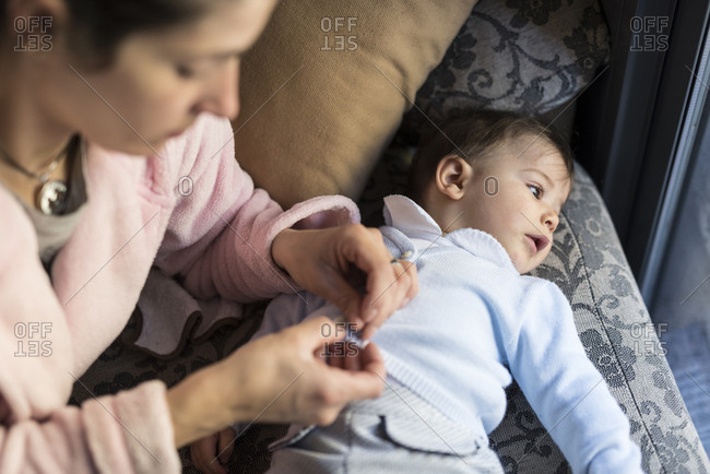 Mother dressing six months old baby on sofa with natural window light