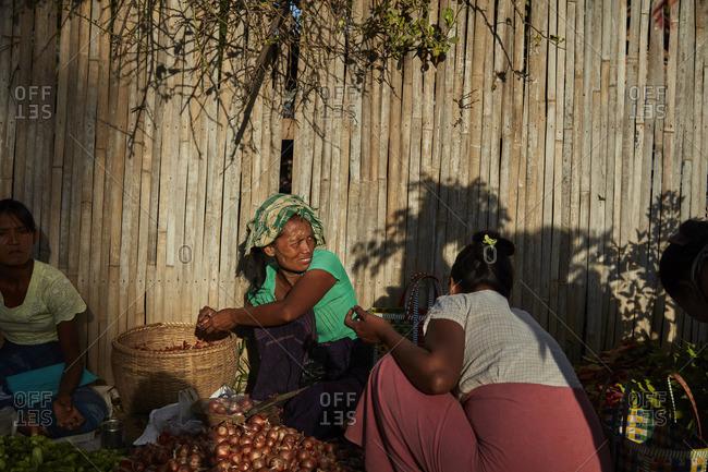 Bagan, Myanmar - August 12, 2015: Women peeling onions at a market in Bagan, Myanmar