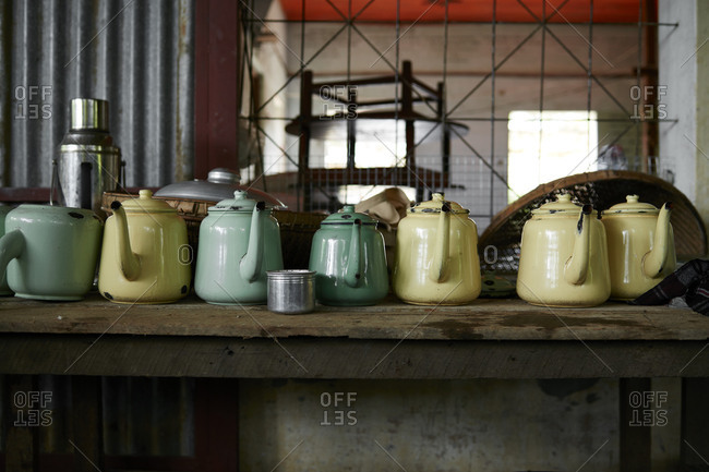 Yellow and green tea kettles on a wooden shelf