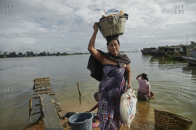 Mandalay, Myanmar - August 10, 2015: Women washing laundry on the Irrawaddy River