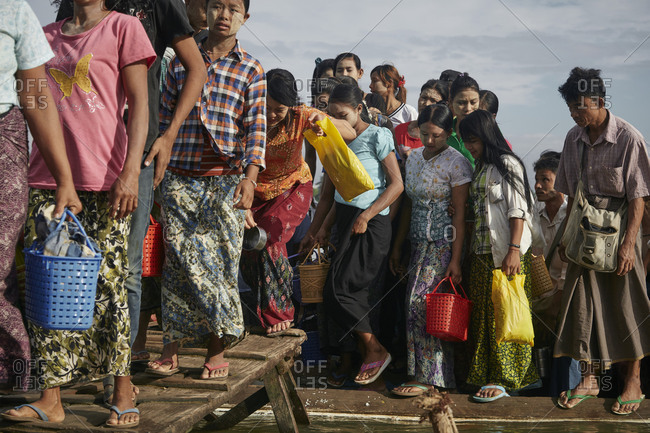Mandalay, Myanmar - August 10, 2015: Women and children walking on dock on the Irrawaddy River