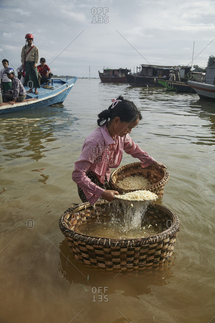 Mandalay, Myanmar - August 10, 2015: Woman washing legumes in the Irrawaddy River