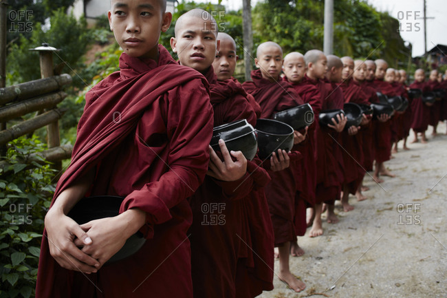 Namhsan, Myanmar - August 8, 2015: Young children monks standing in a line holding black pots