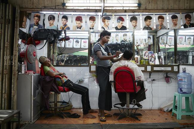 Yangon, Myanmar - August 7, 2015: Hair stylist giving an a haircut in a salon