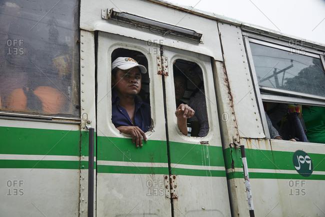 Yangon, Myanmar - August 15, 2015: Man in window of a bus