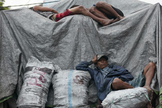 Yangon, Myanmar - August 16, 2015: Man resting on burlap bags