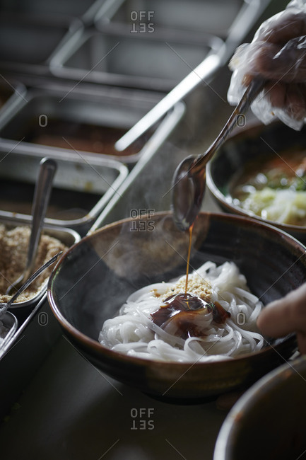 Hands pouring sauce over noodles in a bowl