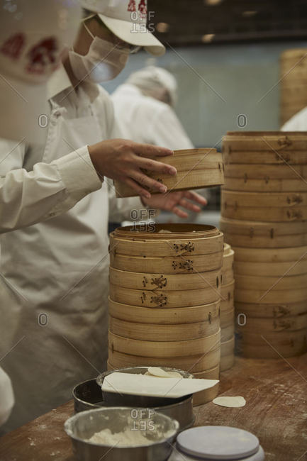 Workers in a restaurant storing food in wooden containers