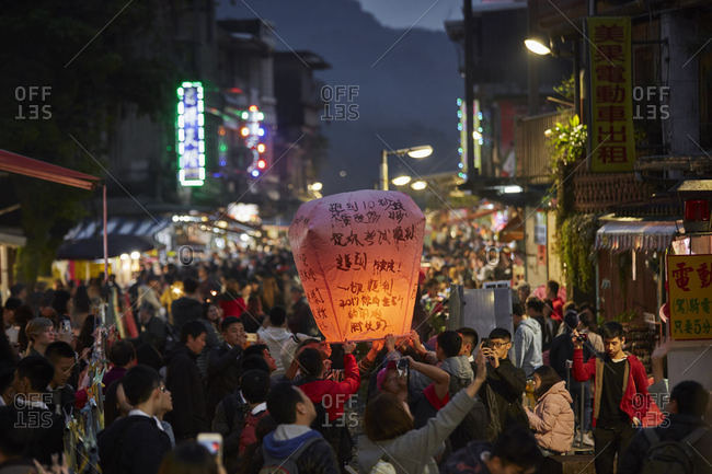 Pingxi District, New Taipei City, Taiwan - December 30, 2016: People holding paper lanterns in the Pingxi District in New Taipei City, Taiwan