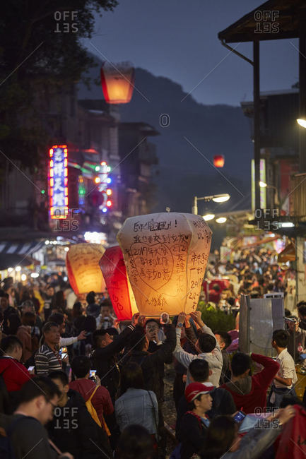 Pingxi District, New Taipei City, Taiwan - December 30, 2016: Crowds holding paper lanterns in the Pingxi District in New Taipei City, Taiwan