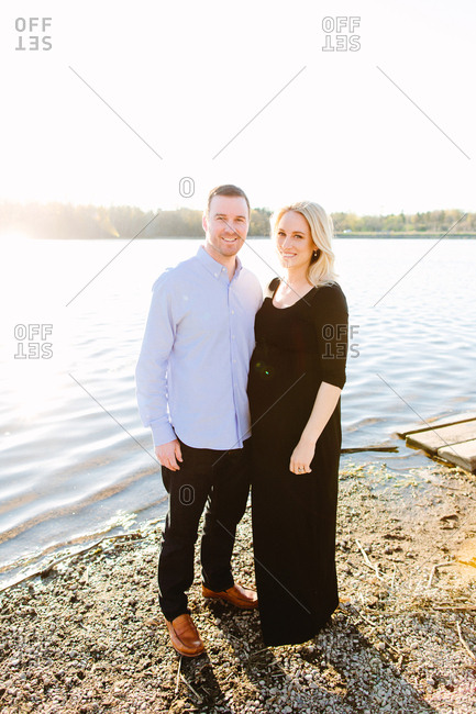 Expectant couple standing and smiling on a lakeshore