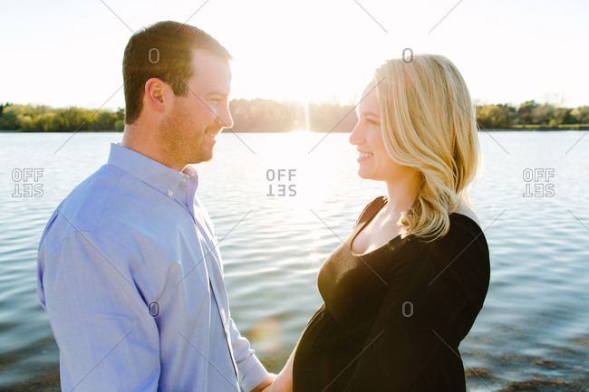 Expectant couple smiling and gazing at each other on a lakeshore