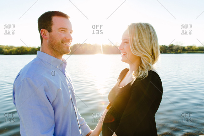 Expectant couple laughing together on a lakeshore