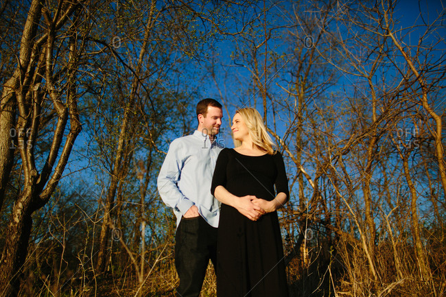 Expectant couple standing together in front of trees smiling