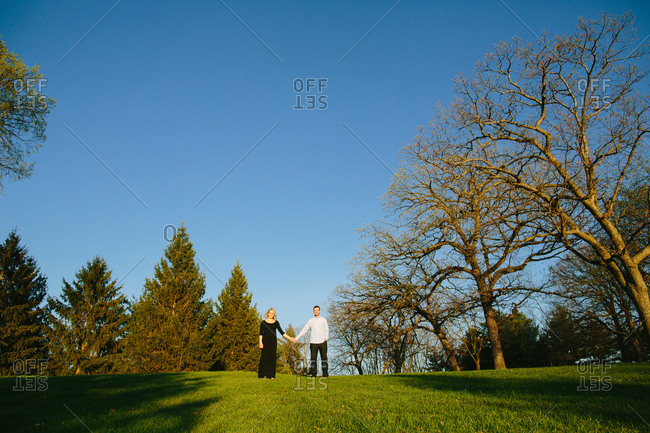 Expectant couple standing together in a field holding hands