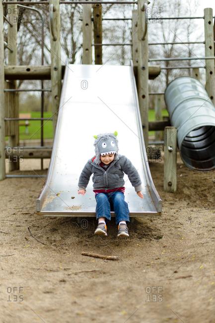 Toddler boy at base of slide