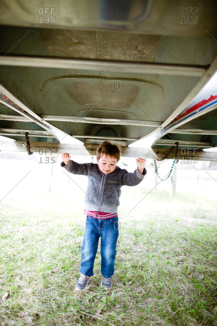 Boy hanging from an upside down canoe