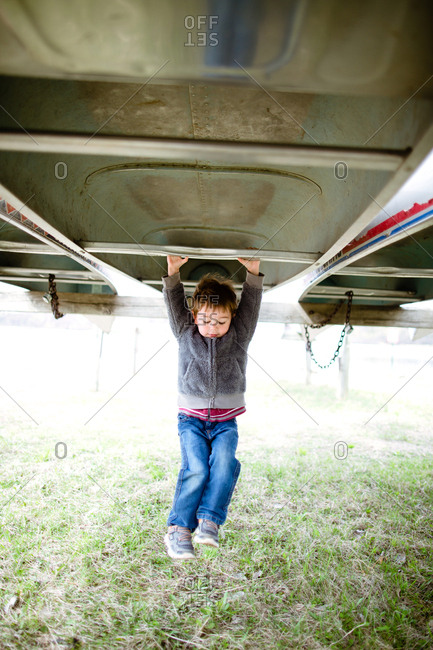 Boy hanging from upside down canoe