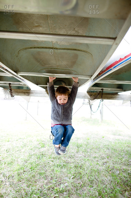 Boy hanging from an upside down kayak