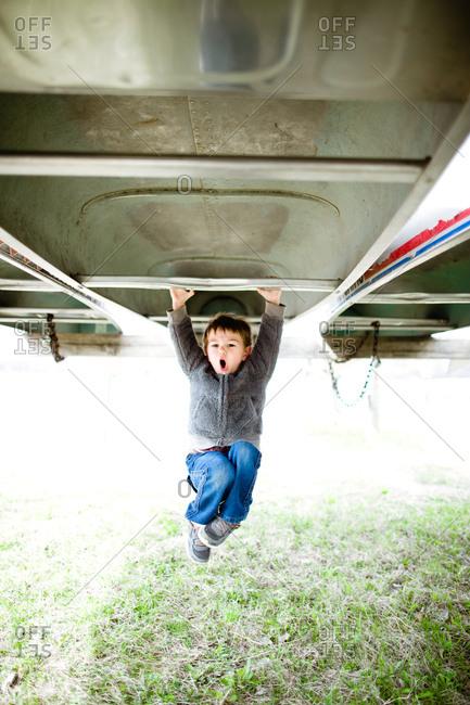 Boy hanging from upside down kayak