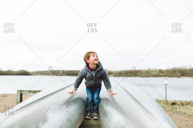 Boy on kayak stand beams