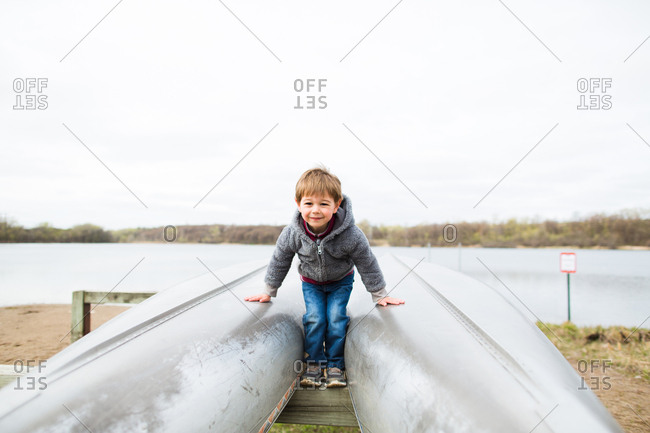 Boy balancing on kayak stand beams
