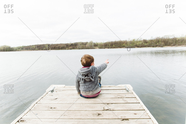 Boy pointing on a lake dock